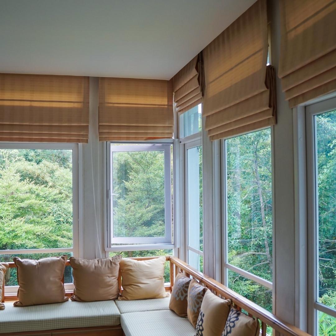 Raffrollo ohne Bohren in braun an großflächiger Fensterfront.